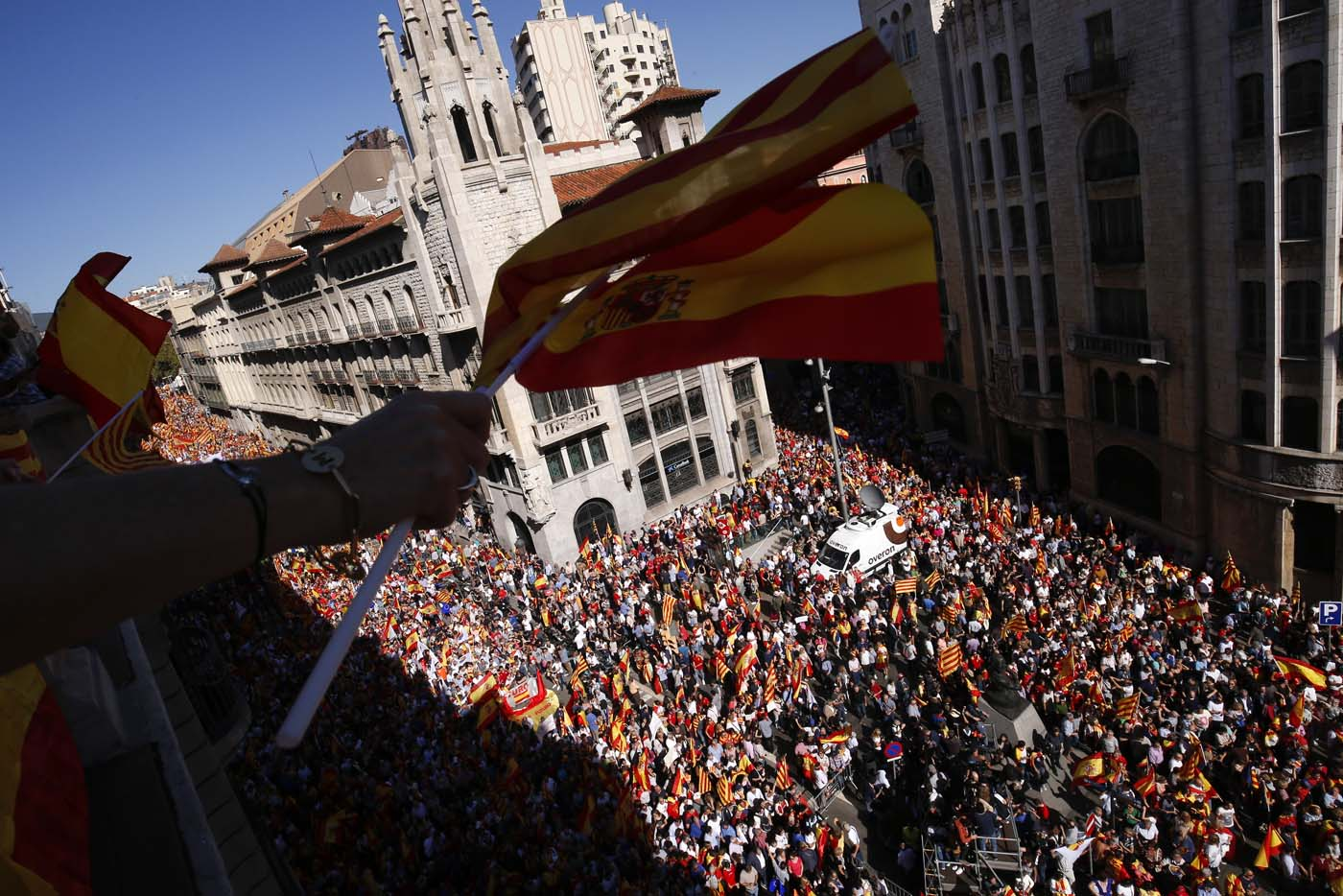 "Protesters hold Spanish flags from a balcony during a demonstration called by ""Societat Civil Catalana"" (Catalan Civil Society) to support the unity of Spain on October 8, 2017 in Barcelona. Spain braced for more protests despite tentative signs that the sides may be seeking to defuse the crisis after Madrid offered a first apology to Catalans injured by police during their outlawed independence vote. / AFP PHOTO / PAU BARRENA"