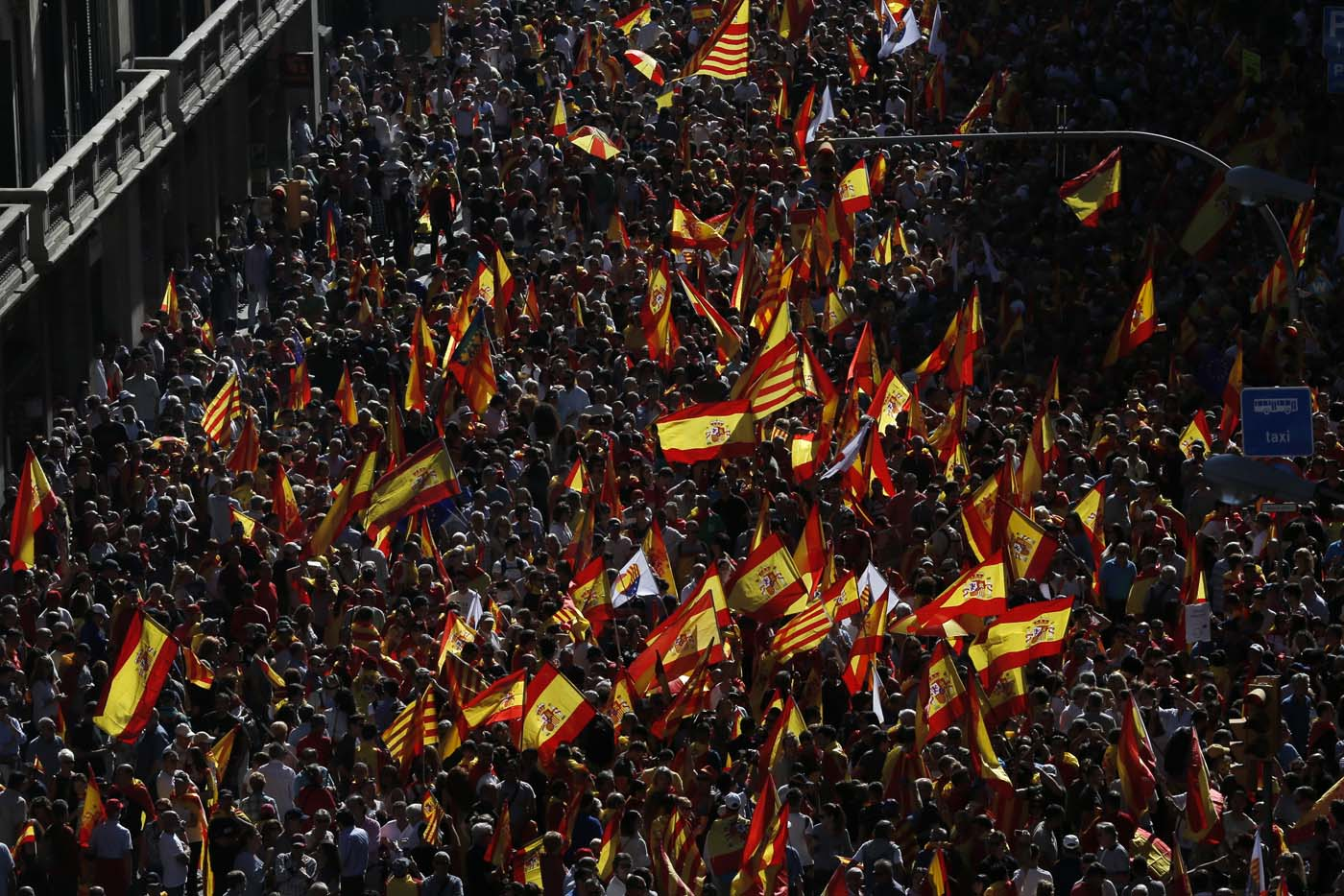 "Protesters hold Spanish flags during a demonstration called by ""Societat Civil Catalana"" (Catalan Civil Society) to support the unity of Spain on October 8, 2017 in Barcelona. Spain braced for more protests despite tentative signs that the sides may be seeking to defuse the crisis after Madrid offered a first apology to Catalans injured by police during their outlawed independence vote. / AFP PHOTO / PAU BARRENA"