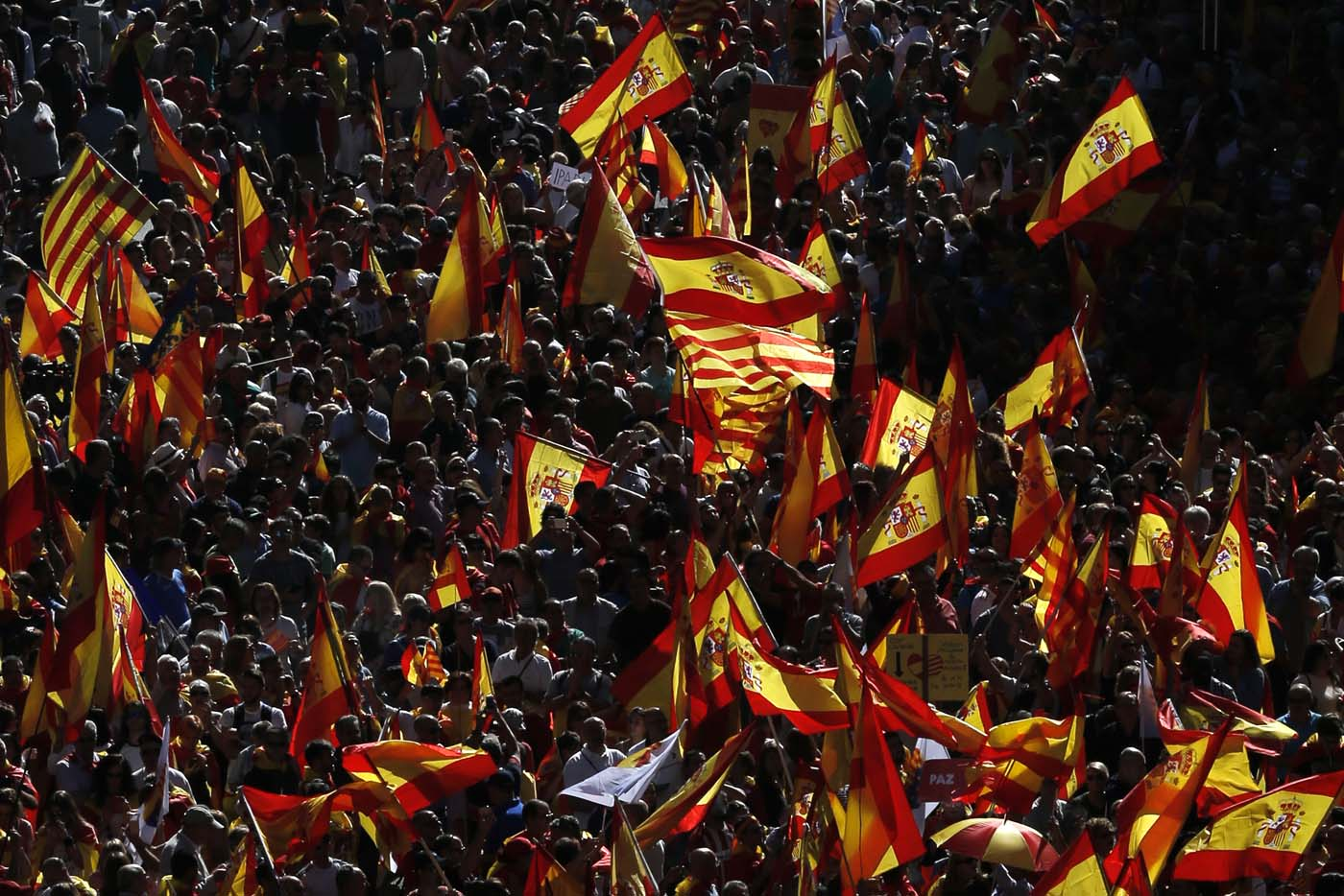"""Protesters hold Spanish and Catalan flags during a demonstration called by """"Societat Civil Catalana"""" (Catalan Civil Society) to support the unity of Spain on October 8, 2017 in Barcelona. Spain braced for more protests despite tentative signs that the sides may be seeking to defuse the crisis after Madrid offered a first apology to Catalans injured by police during their outlawed independence vote. / AFP PHOTO / PAU BARRENA"""