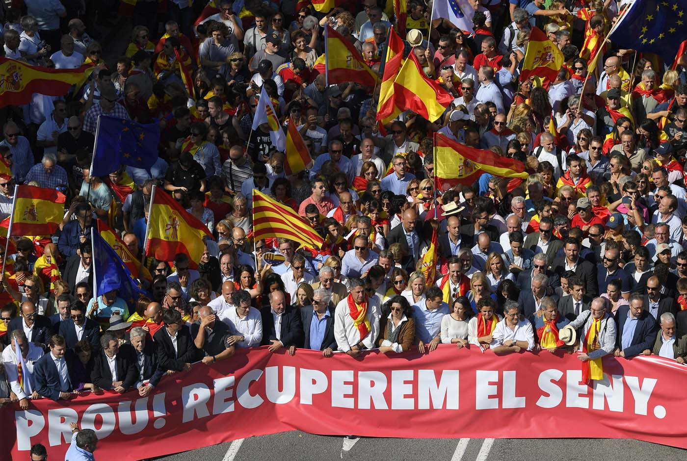 """Leader of the Popular Party of Catalonia (PPC) Xavier Garcia Albiol and Peruvian writer Mario Vargas Llosa (first row,center) walk behind a banner reading in Catalan """"Enough, regain lucidity"""" during a demonstration called by """"Societat Civil Catalans"""" (Catalan Civil Society) to support the unity of Spain on October 8, 2017 in Barcelona. Spain braced for more protests despite tentative signs that the sides may be seeking to defuse the crisis after Madrid offered a first apology to Catalans injured by police during their outlawed independence vote. / AFP PHOTO / LLUIS GENE"""