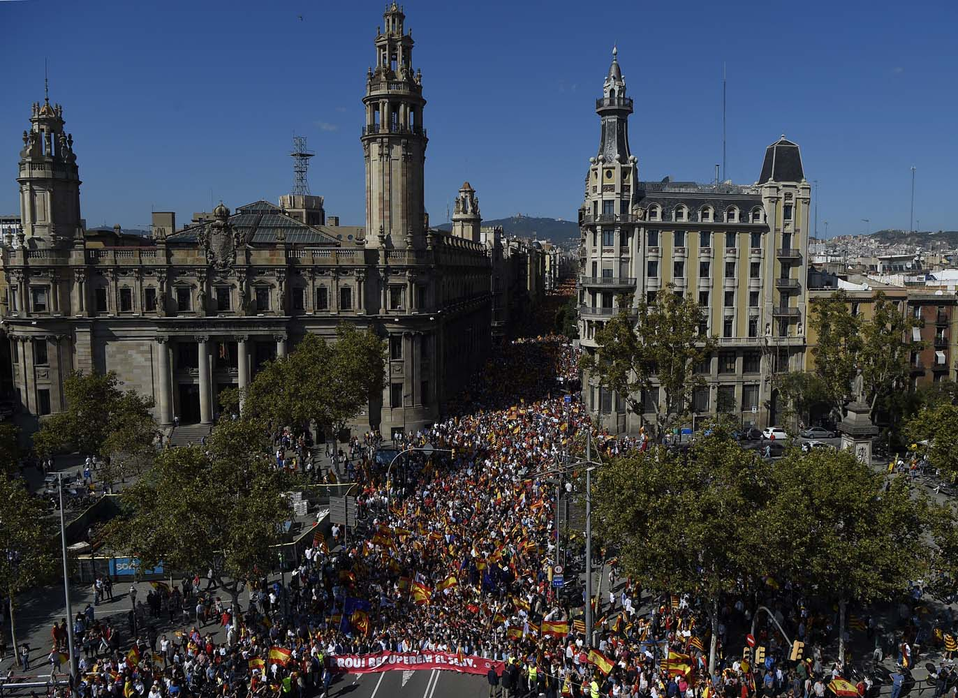 """This general view shows protesters holding a banner reading in Catalan """"Enough, regain lucidity"""" during a demonstration called by """"Societat Civil Catalans"""" (Catalan Civil Society) to support the unity of Spain on October 8, 2017 in Barcelona. Spain braced for more protests despite tentative signs that the sides may be seeking to defuse the crisis after Madrid offered a first apology to Catalans injured by police during their outlawed independence vote. / AFP PHOTO / LLUIS GENE"""