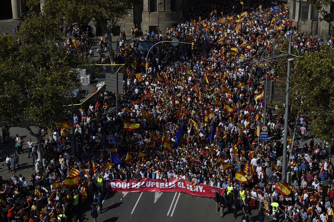 """Protester hold a banner reading in Catalan """"Enough, regain lucidity"""" during a demonstration called by """"Societat Civil Catalans"""" (Catalan Civil Society) to support the unity of Spain on October 8, 2017 in Barcelona. Spain braced for more protests despite tentative signs that the sides may be seeking to defuse the crisis after Madrid offered a first apology to Catalans injured by police during their outlawed independence vote. / AFP PHOTO / LLUIS GENE"""