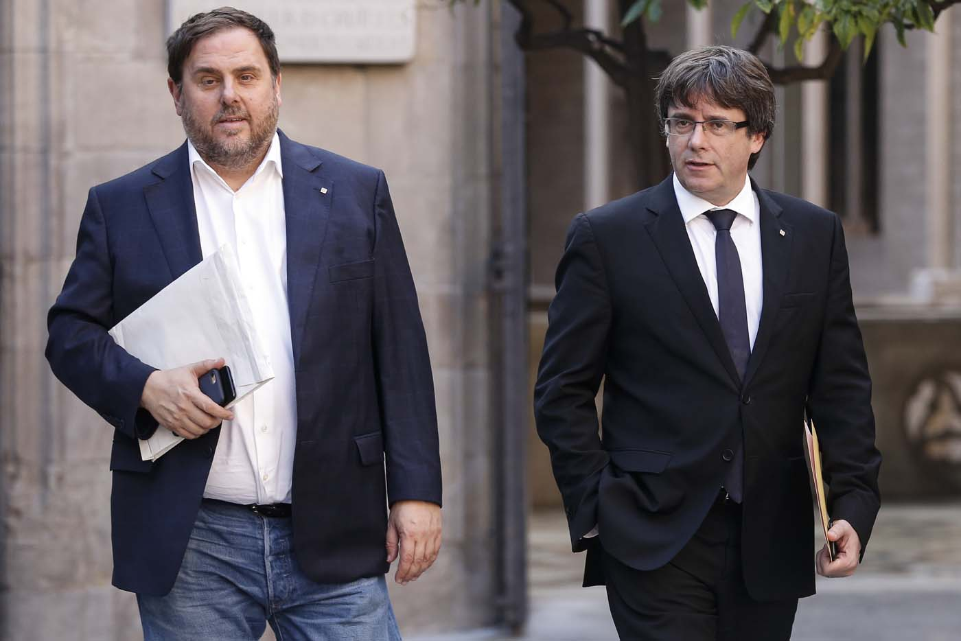 Catalan regional government president Carles Puigdemont (R) and Catalan regional vice president and chief of economy and finance Oriol Junqueras arrive for a regional government meeting at the Generalitat Palace in Barcelona on October 10, 2017. Spain's worst political crisis in a generation will come to a head as Catalonia's leader could declare independence from Madrid in a move likely to send shockwaves through Europe. / AFP PHOTO / PAU BARRENA