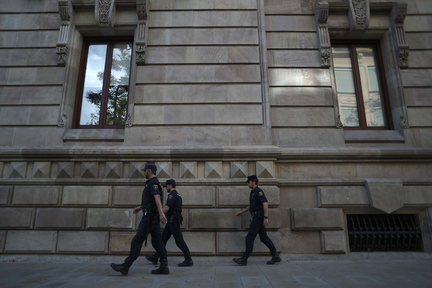Police officers patrol outside the High Court of Catalonia in Barcelona on October 10, 2017. Spain's worst political crisis in a generation will come to a head as Catalonia's leader could declare independence from Madrid in a move likely to send shockwaves through Europe. / AFP PHOTO / JORGE GUERRERO