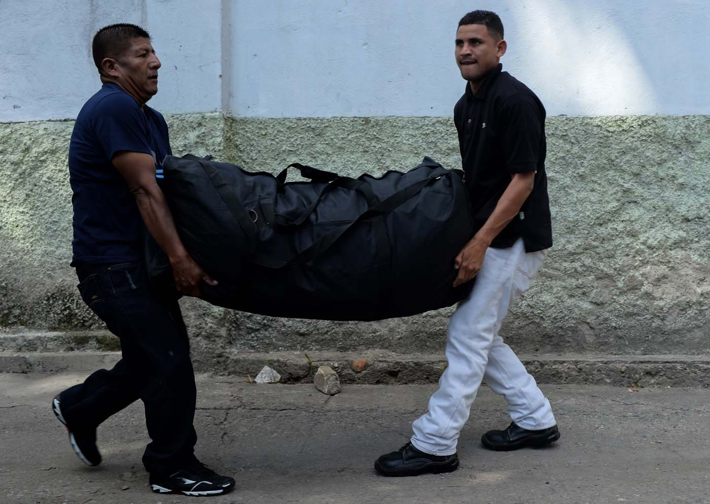 Two men carry a bag as they arrive at a bus station in Caracas on October 11, 2017 as scores of disappointed Venezuelans who see no end to the crisis choose to leave the country. Venezuela, which holds regional elections on October 15, is a country at the top of the Latin American continent that is in deep economic and political crisis. / AFP PHOTO / Federico PARRA