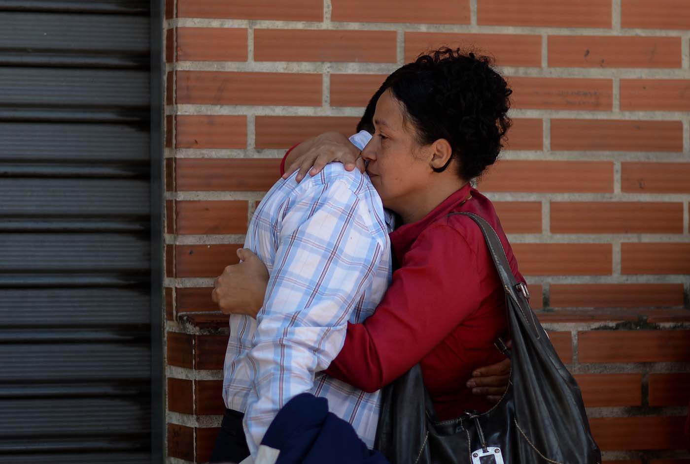 A couple embraces before boarding a bus at a station in Caracas on October 11, 2017 as scores of disappointed Venezuelans who see no end to the crisis choose to leave the country. Venezuela, which holds regional elections on October 15, is a country at the top of the Latin American continent that is in deep economic and political crisis. / AFP PHOTO / Federico PARRA