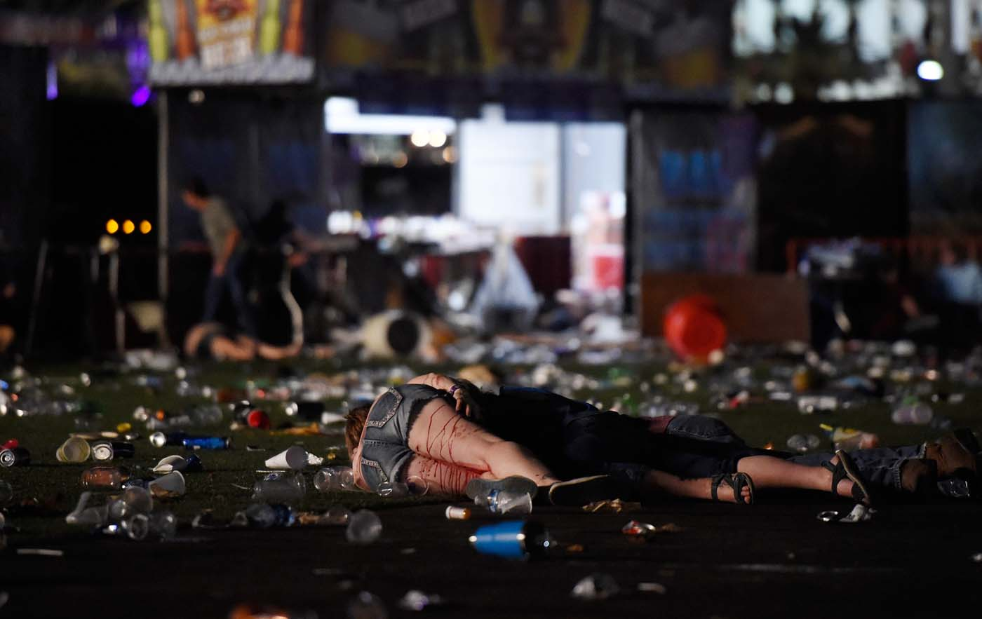 LAS VEGAS, NV - OCTOBER 01: (EDITORS NOTE: Image contains graphic content.) A person lies on the ground covered with blood at the Route 91 Harvest country music festival after apparent gun fire was heard on October 1, 2017 in Las Vegas, Nevada. There are reports of an active shooter around the Mandalay Bay Resort and Casino. David Becker/Getty Images/AFP