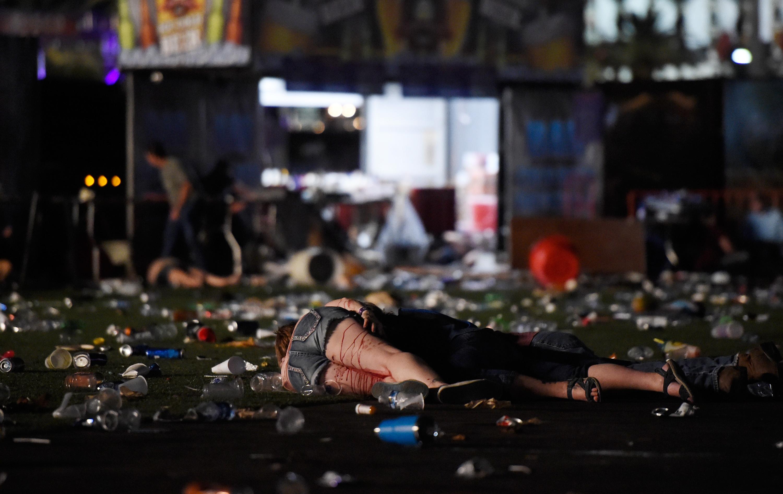 Una persona se encuentra en la tierra cubierta con sangre en el festival de música country de la cosecha de la ruta 91 después de que el fuego aparente del arma fuera oído el 1 de octubre de 2017 en Las Vegas, Nevada. Hay informes de un tirador activo alrededor del Mandalay Bay Resort y Casino. David Becker / Getty Images / AFP