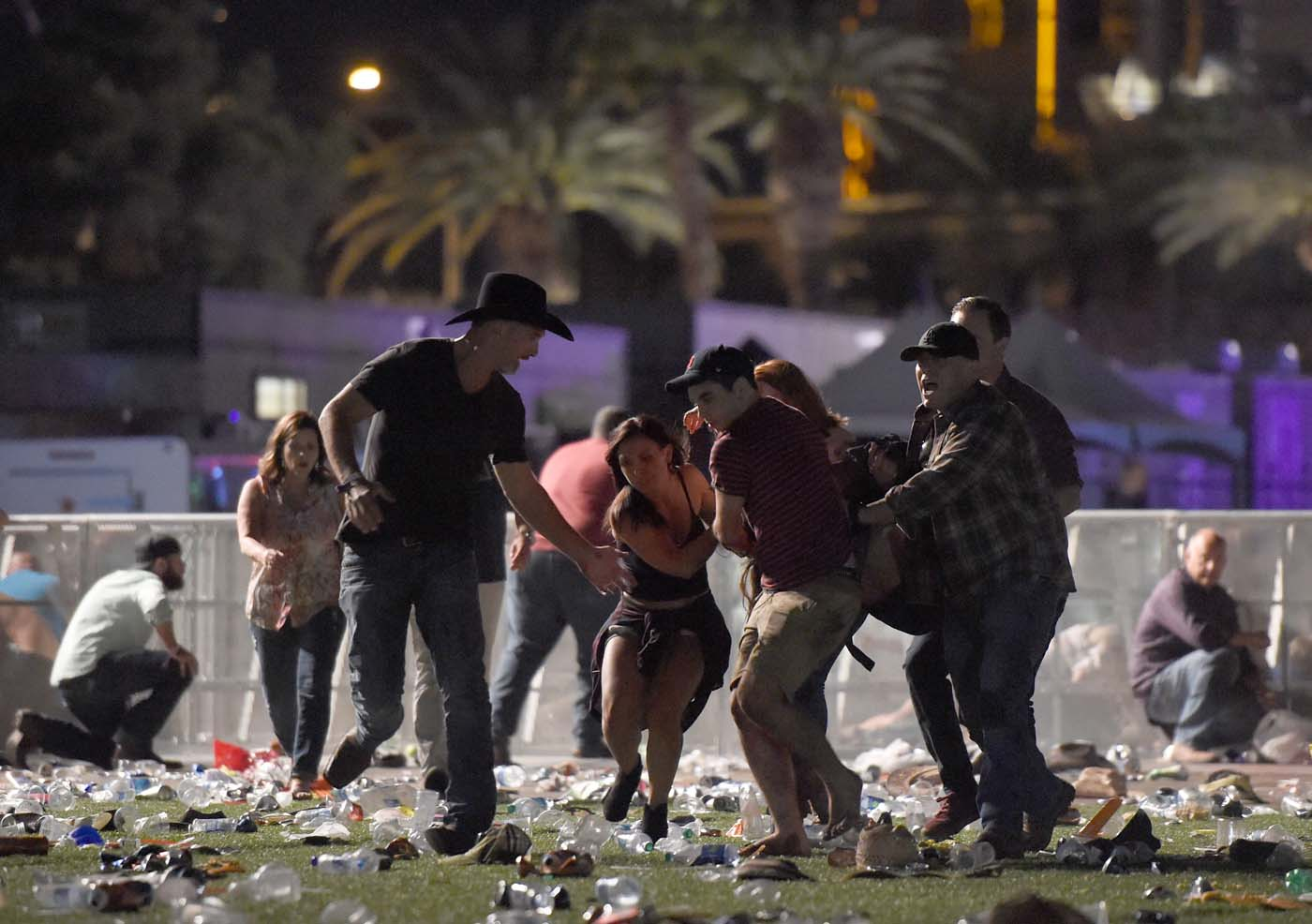 LAS VEGAS, NV - OCTOBER 01: (EDITORS NOTE: Image contains graphic content.) People carry a peson at the Route 91 Harvest country music festival after apparent gun fire was heard on October 1, 2017 in Las Vegas, Nevada. There are reports of an active shooter around the Mandalay Bay Resort and Casino. David Becker/Getty Images/AFP