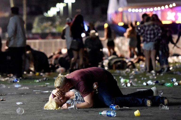 LAS VEGAS, NV - 01 de octubre: Un hombre se pone encima de una mujer como otros huyen de los motivos del festival de música country de la cosecha de la Ruta 91 después de que un tirador activo fue informado el 1 de octubre de 2017 en Las Vegas, Nevada. Un pistolero abrió fuego en un festival de música en Las Vegas, dejando al menos 2 muertos. La policía ha confirmado que un sospechoso ha recibido un disparo. La investigación está en curso. David Becker / Getty Images / AFP
