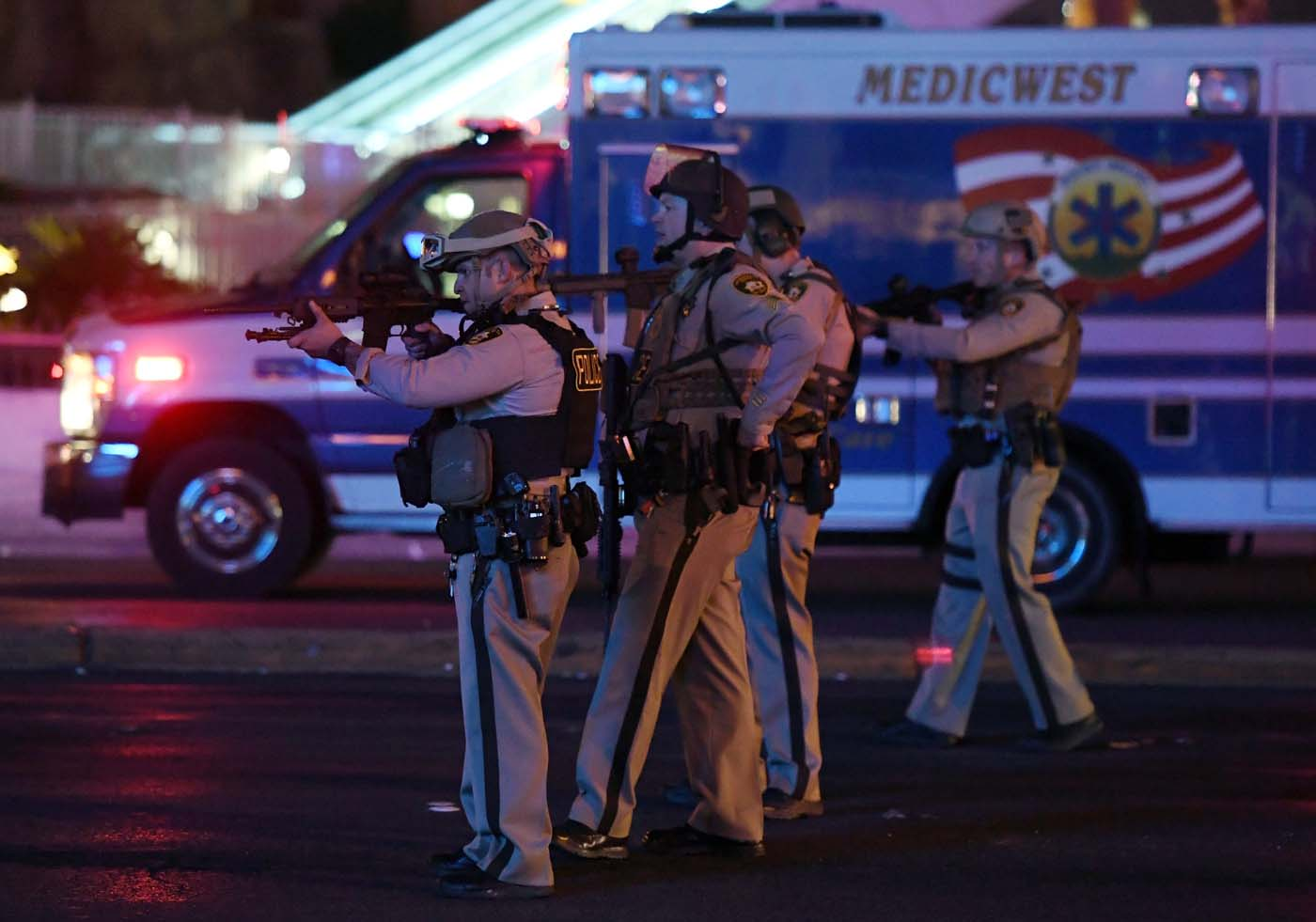 LAS VEGAS, NV - OCTOBER 02: Police officers point their weapons at a car driving down closed Tropicana Ave. near Las Vegas Boulevard after a reported mass shooting at a country music festival nearby on October 2, 2017 in Las Vegas, Nevada. A gunman has opened fire on a music festival in Las Vegas, leaving at least 2 people dead. Police have confirmed that one suspect has been shot. The investigation is ongoing. Ethan Miller/Getty Images/AFP