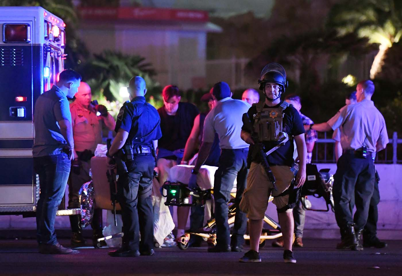LAS VEGAS, NV - OCTOBER 02: Police officers stand by as medical personnel tend to a person on Tropicana Ave. near Las Vegas Boulevard after a mass shooting at a country music festival nearby on October 2, 2017 in Las Vegas, Nevada .A gunman has opened fire on a music festival in Las Vegas, leaving over 20 people dead. Police have confirmed that one suspect has been shot. The investigation is ongoing. Ethan Miller/Getty Images/AFP