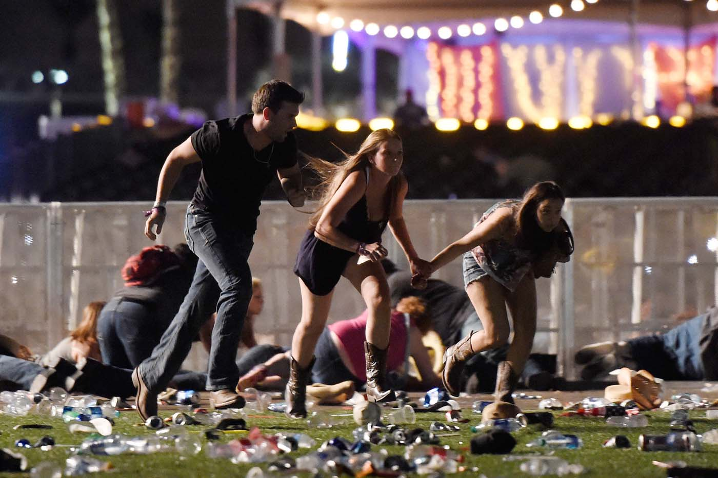 LAS VEGAS, NV - OCTOBER 01: People run from the Route 91 Harvest country music festival after apparent gun fire was hear on October 1, 2017 in Las Vegas, Nevada. A gunman has opened fire on a music festival in Las Vegas, leaving at least 20 people dead and more than 100 injured. Police have confirmed that one suspect has been shot. The investigation is ongoing. David Becker/Getty Images/AFP