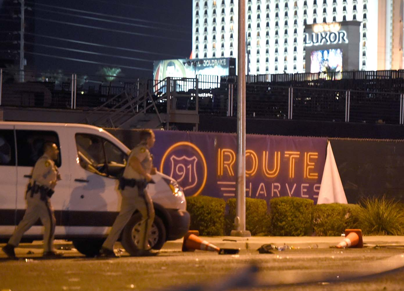 LAS VEGAS, NV - OCTOBER 02: Las Vegas police run by a banner on the fence at the Route 91 Harvest country music festival grounds after a active shooter was reported on October 2, 2017 in Las Vegas, Nevada. A gunman has opened fire on a music festival in Las Vegas, leaving at least 20 people dead and more than 100 injured. Police have confirmed that one suspect has been shot. The investigation is ongoing. David Becker/Getty Images/AFP