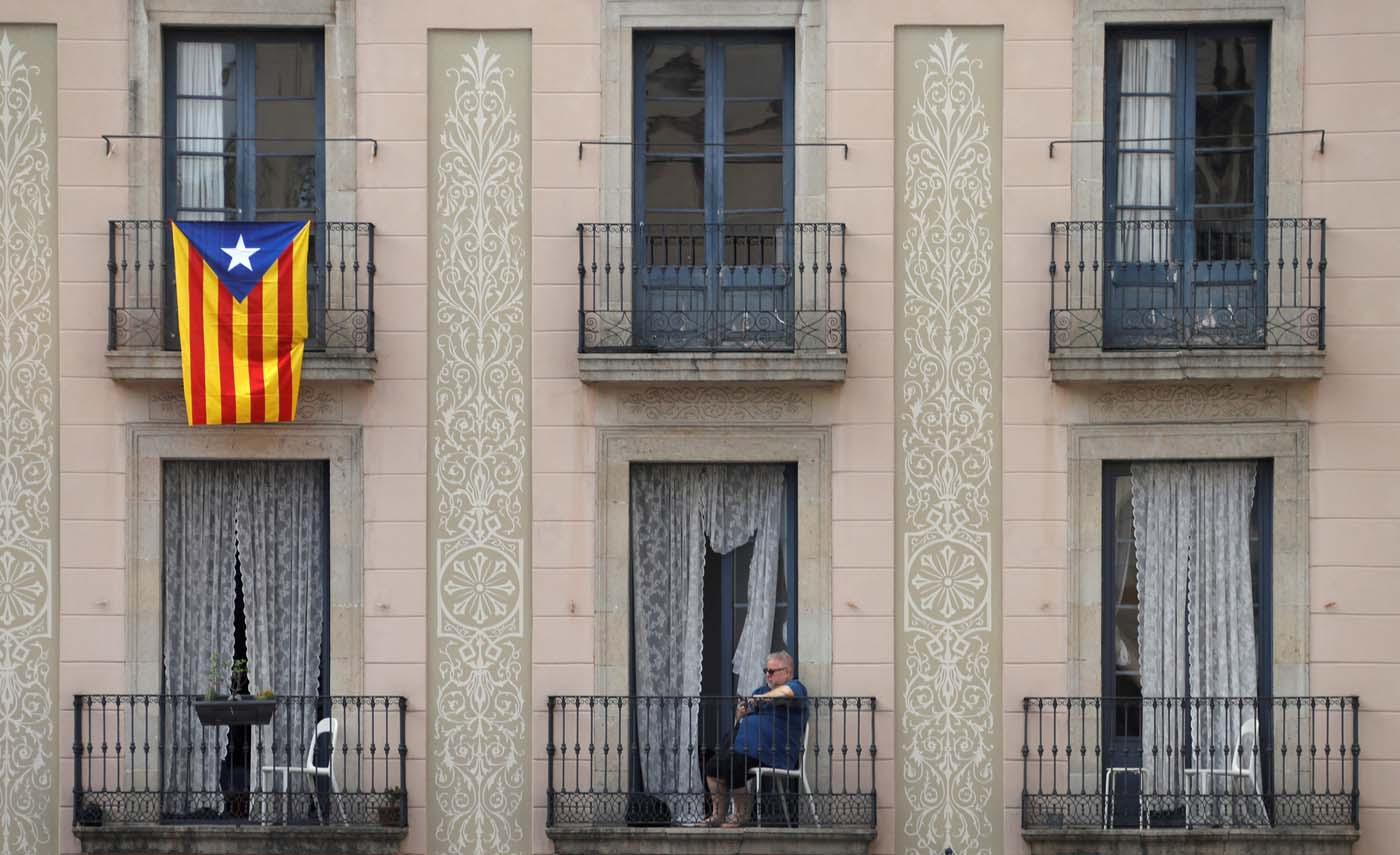 A Catalan flag hangs from a balcony as a woman watches a demonstration in a square in Barcelona, Spain, October 7, 2017 REUTERS/Eric Gaillard