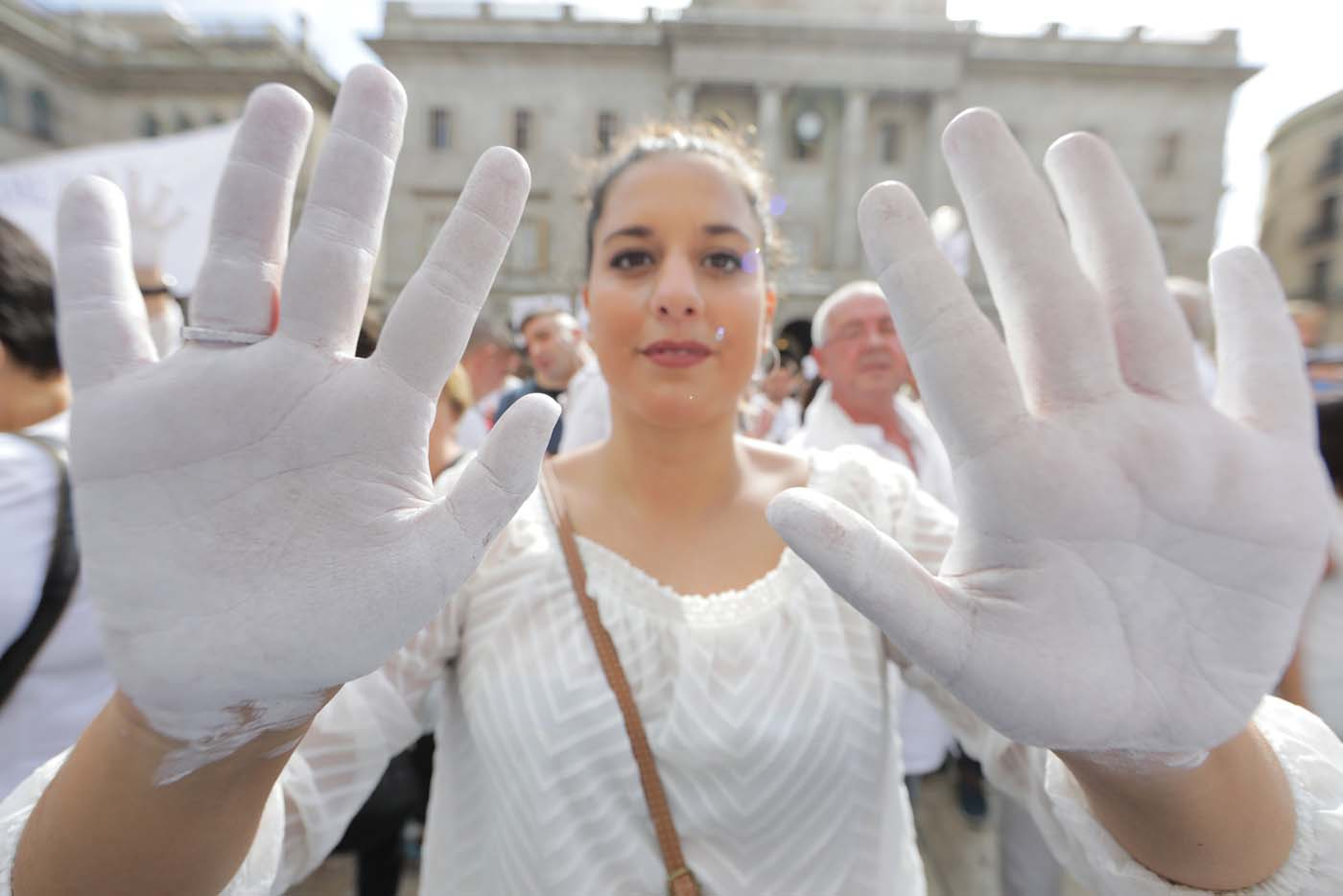 A woman shows her white painted hands duing a demonstration in favour of dialogue in a square in Barcelona, Spain, October 7, 2017 REUTERS/Eric Gaillard