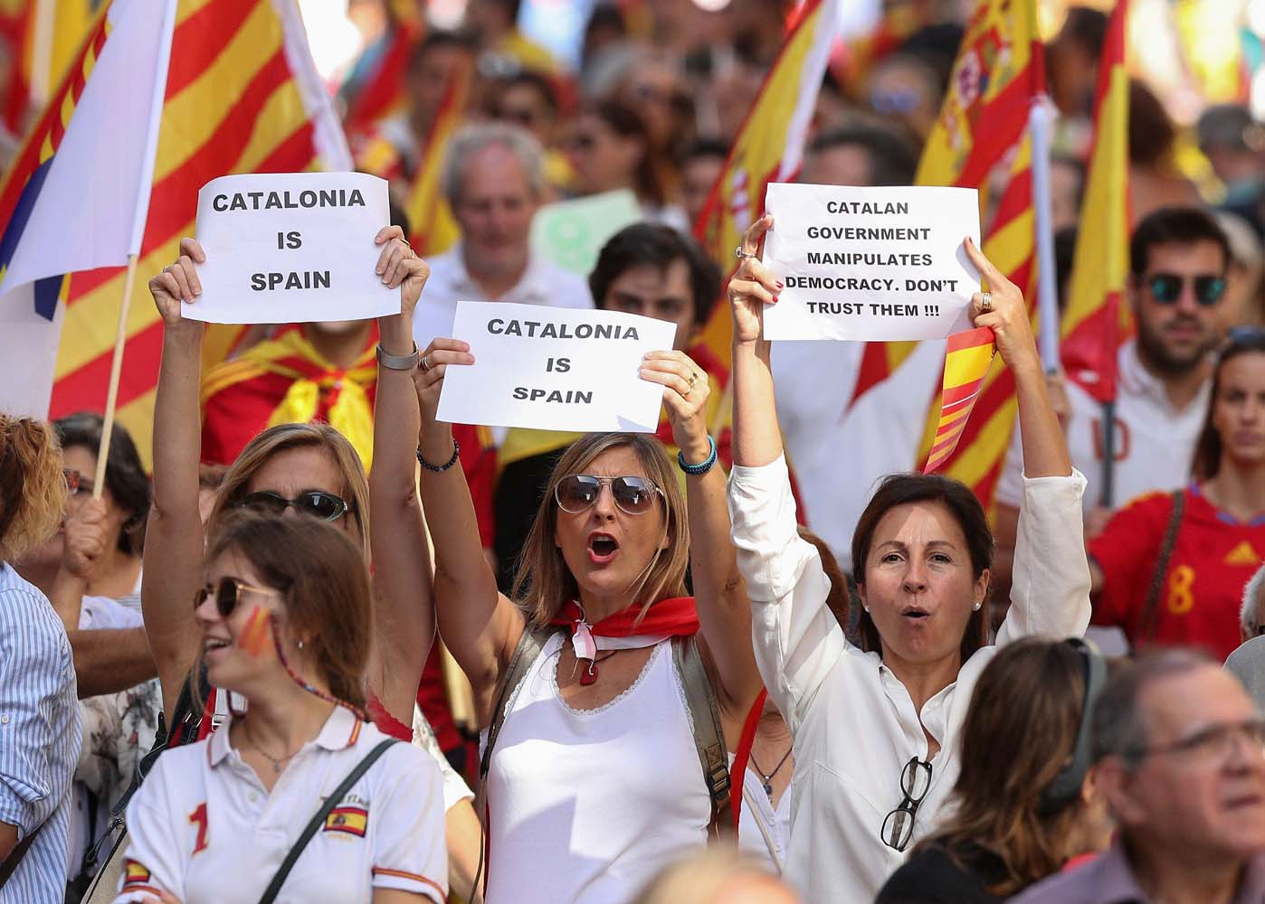 People hold up signs as they attend a pro-union demonstration organised by the Catalan Civil Society organisation in Barcelona, Spain, October 8, 2017. REUTERS/Albert Gea