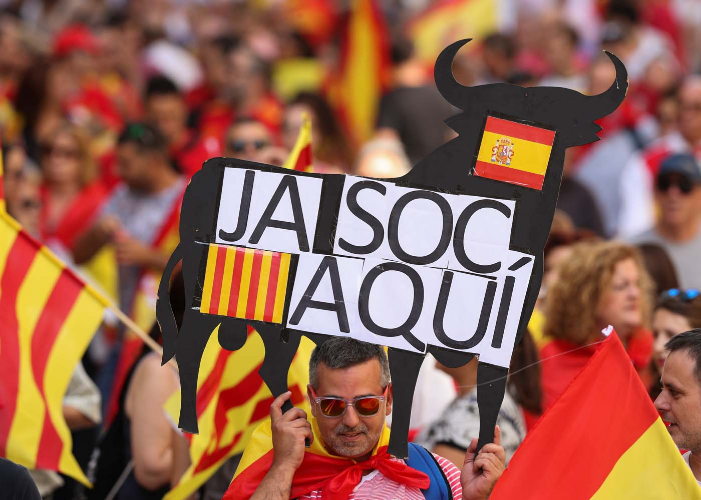 """A man holds up a banner in the form of a bull reading """"I am here"""" during a pro-union demonstration organised by the Catalan Civil Society organisation in Barcelona, Spain, October 8, 2017. REUTERS/Albert Gea"""