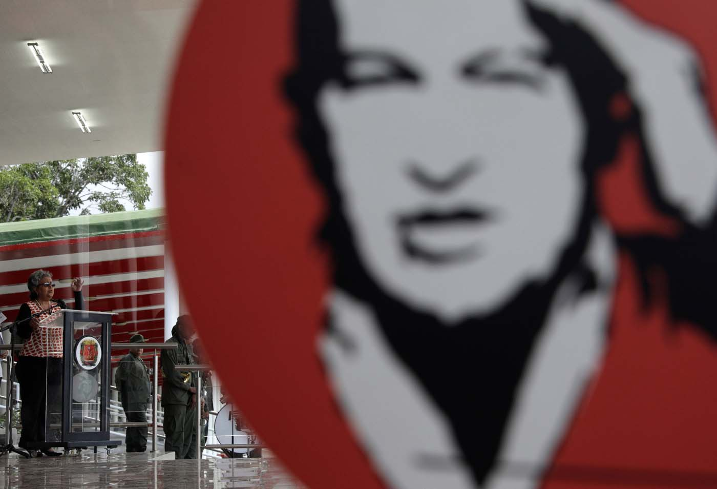 Venezuela's National Electoral Council (CNE) President Tibisay Lucena is pictured through a glass with a picture of Venezuela's late President Hugo Chavez, as she speaks during a ceremony ahead of the regional elections which will be held on October 15, in Caracas, Venezuela October 9, 2017. REUTERS/Ricardo Moraes