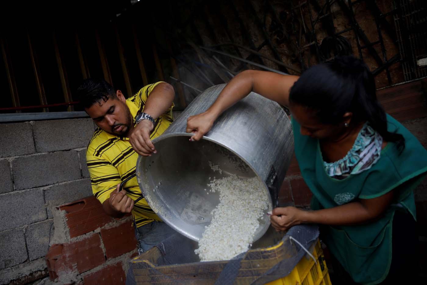 Medical equipment repairman Leandro Colmenares (L) makes corn dough at the backyard of his house in Caracas, Venezuela October 3, 2017. Picture taken October 3, 2017. REUTERS/Carlos Garcia Rawlins