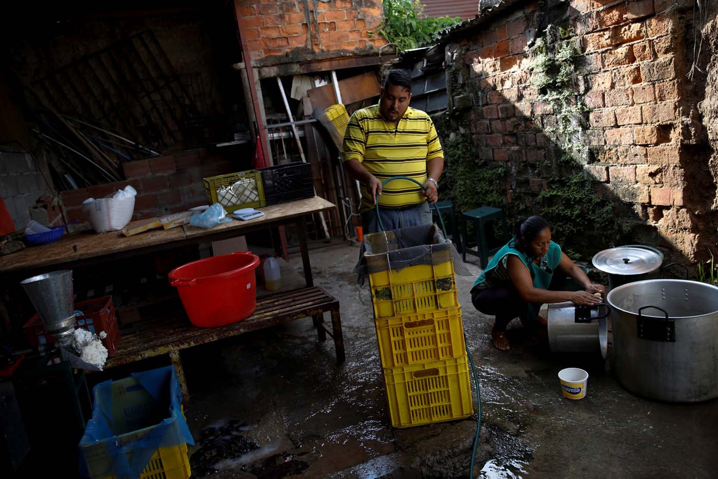 Medical equipment repairman Leandro Colmenares (C) makes corn dough at the backyard of his house in Caracas, Venezuela October 3, 2017. Picture taken October 3, 2017. REUTERS/Carlos Garcia Rawlins