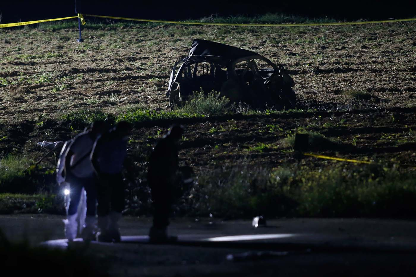 Forensic experts use lights as they look for evidence on a road near a field after a powerful bomb blew up a car (Rear) and killed investigative journalist Daphne Caruana Galizia in Bidnija, Malta, October 16, 2017. REUTERS/Darrin Zammit Lupi