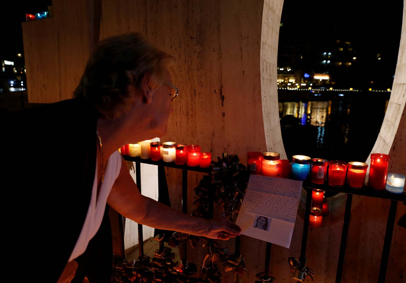 A woman reads a letter to investigative journalist Daphne Caruana Galizia, assassinated in a car bomb attack, on the Love monument during a silent candlelight vigil to protest against her murder, in St Julian's, Malta, October 16, 2017. REUTERS/Darrin Zammit Lupi