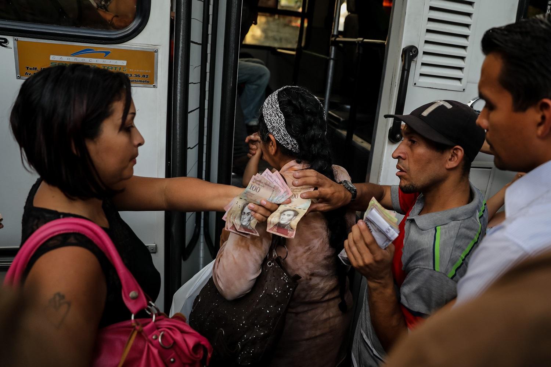 Fotografías del 10 de octubre del 2017, de un grupo de personas que pagan su pasaje para subir a un bus de transporte público en la ciudad de Caracas (Venezuela). Los altos costos de mantenimiento, la disminución de importación de repuestos, una galopante inflación y la escasez de efectivo tienen al sistema de transporte de Venezuela en jaque, mientras la población padece los efectos de esta crisis con un pasaje inestable y largos tiempos de espera para trasladarse. EFE/MIGUEL GUTIÉRREZ