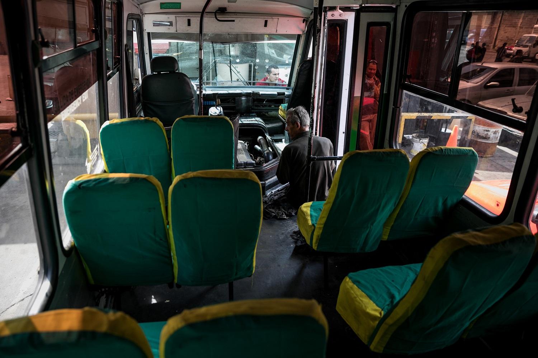 Fotografías del 10 de octubre del 2017, de un mecánico que trabaja en un bus de transporte público, en la ciudad de Caracas (Venezuela). Los altos costos de mantenimiento, la disminución de importación de repuestos, una galopante inflación y la escasez de efectivo tienen al sistema de transporte de Venezuela en jaque, mientras la población padece los efectos de esta crisis con un pasaje inestable y largos tiempos de espera para trasladarse. EFE/MIGUEL GUTIÉRREZ
