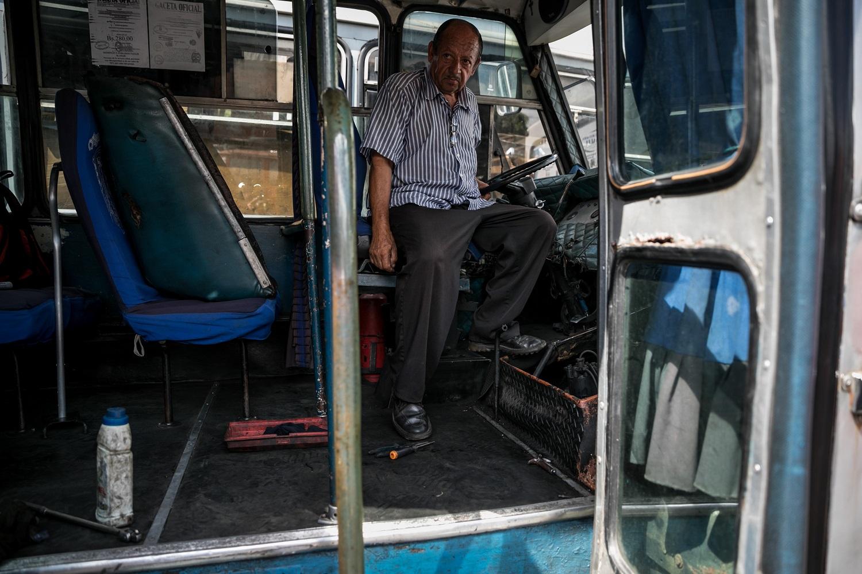 Fotografías del 10 de octubre del 2017, del conductor de un bus de transporte público, mientras espera por un mecánico, en la ciudad de Caracas (Venezuela). Los altos costos de mantenimiento, la disminución de importación de repuestos, una galopante inflación y la escasez de efectivo tienen al sistema de transporte de Venezuela en jaque, mientras la población padece los efectos de esta crisis con un pasaje inestable y largos tiempos de espera para trasladarse. EFE/MIGUEL GUTIÉRREZ
