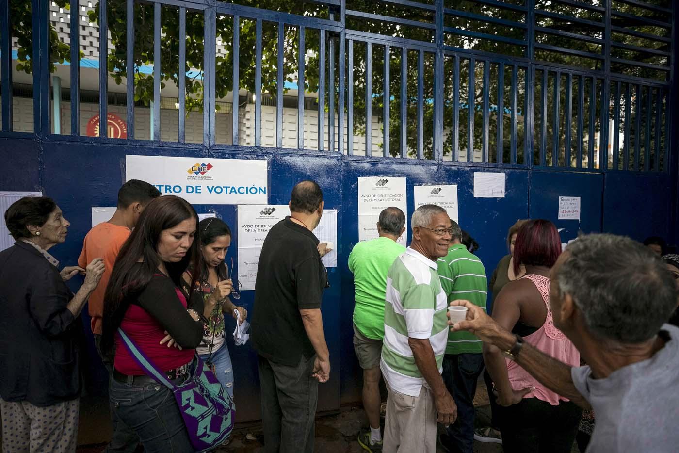 GRA120. CARACAS (VENEZUELA), 15/10/2017 - Varias personas asisten a un centro de votación hoy, 15 de octubre de 2017, en Caracas (Venezuela). Los centros de votación en Venezuela comenzaron hoy a abrir sus puertas a las seis de la mañana hora local (10.00 GMT), como estaba previsto, para atender a los ciudadanos que están llamados a participar en la elección de los 23 gobernadores del país caribeño. EFE/Miguel Gutiérrez