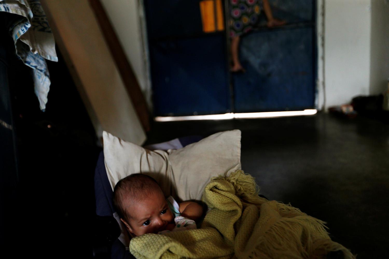 Yennifer Padrón y el bebé de Víctor Córdova descansan en el vestíbulo de la casa que comparten en la favela de Petare en Caracas, Venezuela, 21 de agosto de 2017. Foto tomada el 21 de agosto de 2017. Para coincidir con la Característica VENEZUELA-CHILDREN / REUTERS / Andres Martínez Casares