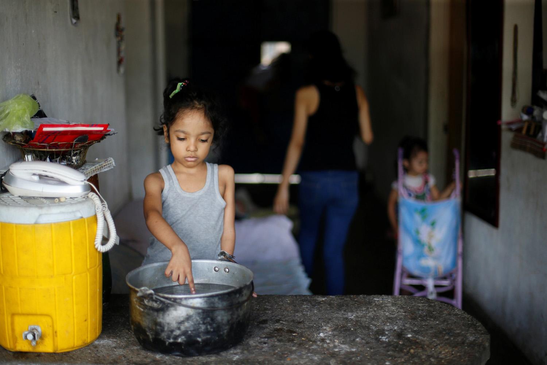 Una de las hijas de Yennifer Padrón y Víctor Córdova toca agua caliente en una olla en la casa donde viven en la favela de Petare en Caracas, Venezuela, el 21 de agosto de 2017. Foto tomada el 21 de agosto de 2017. Para coincidir con la Característica VENEZUELA-CHILDREN / REUTERS / Andres Martinez Casares