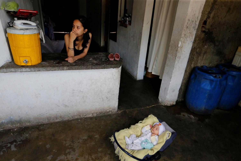 Yennifer Padrón descansa mientras su bebé duerme en la casa donde viven en la favela de Petare en Caracas, Venezuela, 21 de agosto de 2017. Foto tomada el 21 de agosto de 2017. Para coincidir con la Característica VENEZUELA-NIÑOS / REUTERS / Andres Martínez Casares