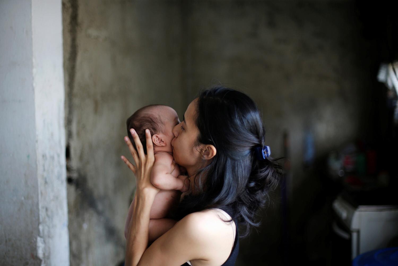Yennifer Padrón besa a su bebé en su casa en la favela de Petare en Caracas, Venezuela, 21 de agosto de 2017. Foto tomada el 21 de agosto de 2017. Para coincidir con la característica VENEZUELA-NIÑOS / REUTERS / Andres Martínez Casares