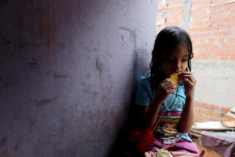 Una de las hijas de Yennifer Padrón y Víctor Córdova come una arepa en la habitación familiar de la casa que comparten en la favela de Petare en Caracas, Venezuela, el 21 de agosto de 2017. Foto tomada el 21 de agosto de 2017. Para coincidir con la Característica VENEZUELA-CHILDREN / REUTERS / Andres Martinez Casares