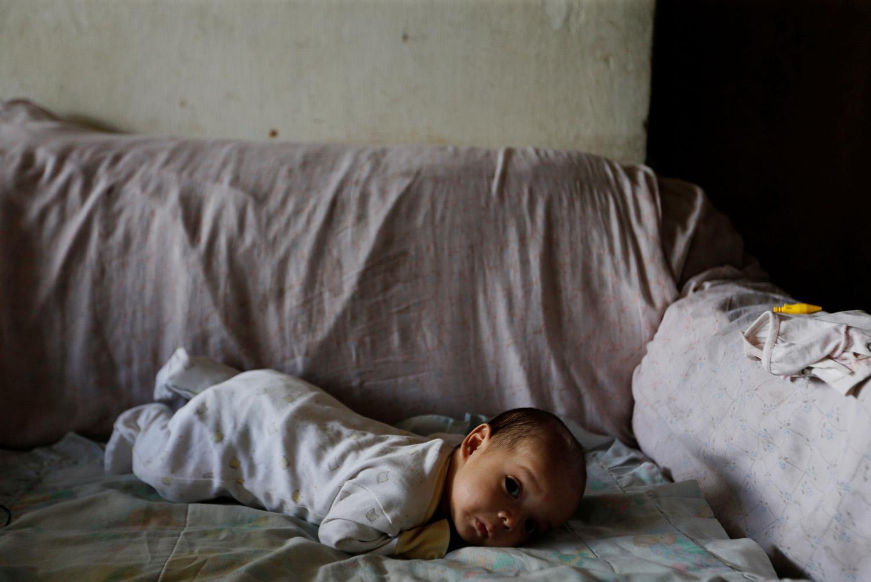 Yennifer Padrón y el hijo de Víctor Córdova descansan en el salón de la casa donde viven en la favela de Petare en Caracas, Venezuela, 21 de agosto de 2017. Foto tomada el 21 de agosto de 2017. Para coincidir con la Característica VENEZUELA-NIÑOS / REUTERS / Andres Martínez Casares