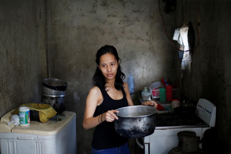 Yennifer Padrón lleva agua caliente para un baño en su casa en la favela de Petare en Caracas, Venezuela, 21 de agosto de 2017. Foto tomada el 21 de agosto de 2017. Para coincidir con la característica VENEZUELA-NIÑOS / REUTERS / Andres Martínez Casares