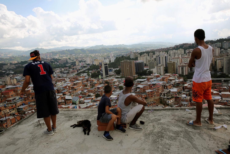 Cuatro muchachos miran hacia adelante como uno vuela una cometa sobre casas en el barrio pobre de Caracas, Venezuela, 29 de agosto de 2017. Foto tomada el 29 de agosto de 2017. Para coincidir con la característica VENEZUELA-NIÑOS / REUTERS / Andres Martínez Casares