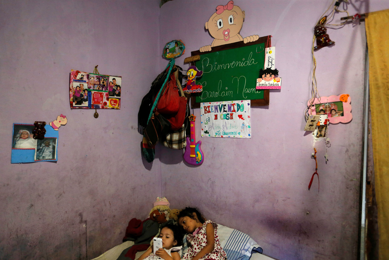 Dos de las hijas de Yennifer Padrón y Víctor Córdova juegan con un teléfono celular en la habitación familiar de la casa que comparten en la favela de Petare en Caracas, Venezuela, el 21 de agosto de 2017. Foto tomada el 21 de agosto de 2017. Para coincidir con la Característica VENEZUELA-CHILDREN / REUTERS / Andres Martinez Casares