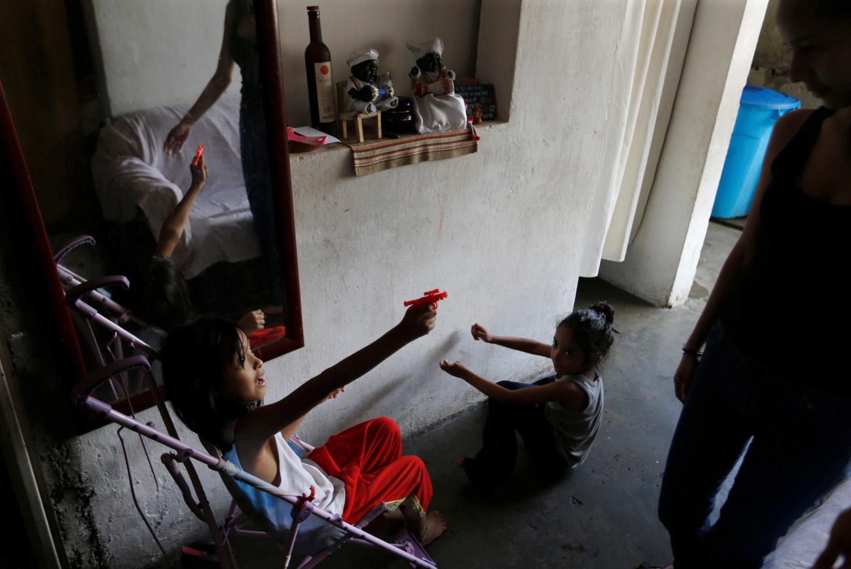 Los niños de Yennifer Padrón y Victor Cordova juegan en la sala de la casa que comparten en la favela de Petare en Caracas, Venezuela, 21 de agosto de 2017. Foto tomada el 21 de agosto de 2017. Para coincidir con la característica VENEZUELA-NIÑOS / REUTERS / Andres Martínez Casares