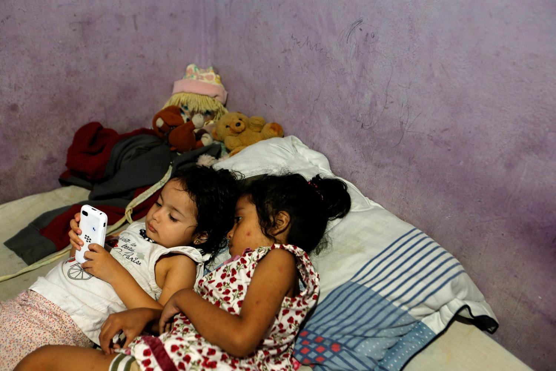 Dos de las hijas de Yennifer Padrón y Víctor Córdova juegan con un teléfono celular en la sala familiar de la casa que comparten en el barrio de Petare en Caracas, Venezuela, el 21 de agosto de 2017. Foto tomada el 21 de agosto de 2017. Para coincidir con la Característica VENEZUELA-CHILDREN / REUTERS / Andres Martinez Casares