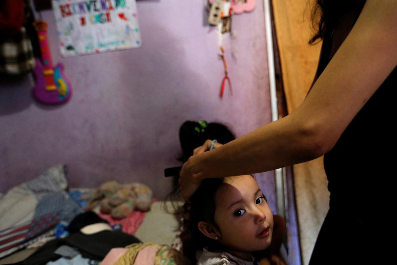 Yennifer Padrón peina el cabello de una de sus hijas en el cuarto familiar de la casa que comparten en la favela de Petare en Caracas, Venezuela, 21 de agosto de 2017. Foto tomada el 21 de agosto de 2017. Para coincidir con la Característica VENEZUELA-CHILDREN / REUTERS / Andres Martinez Casares