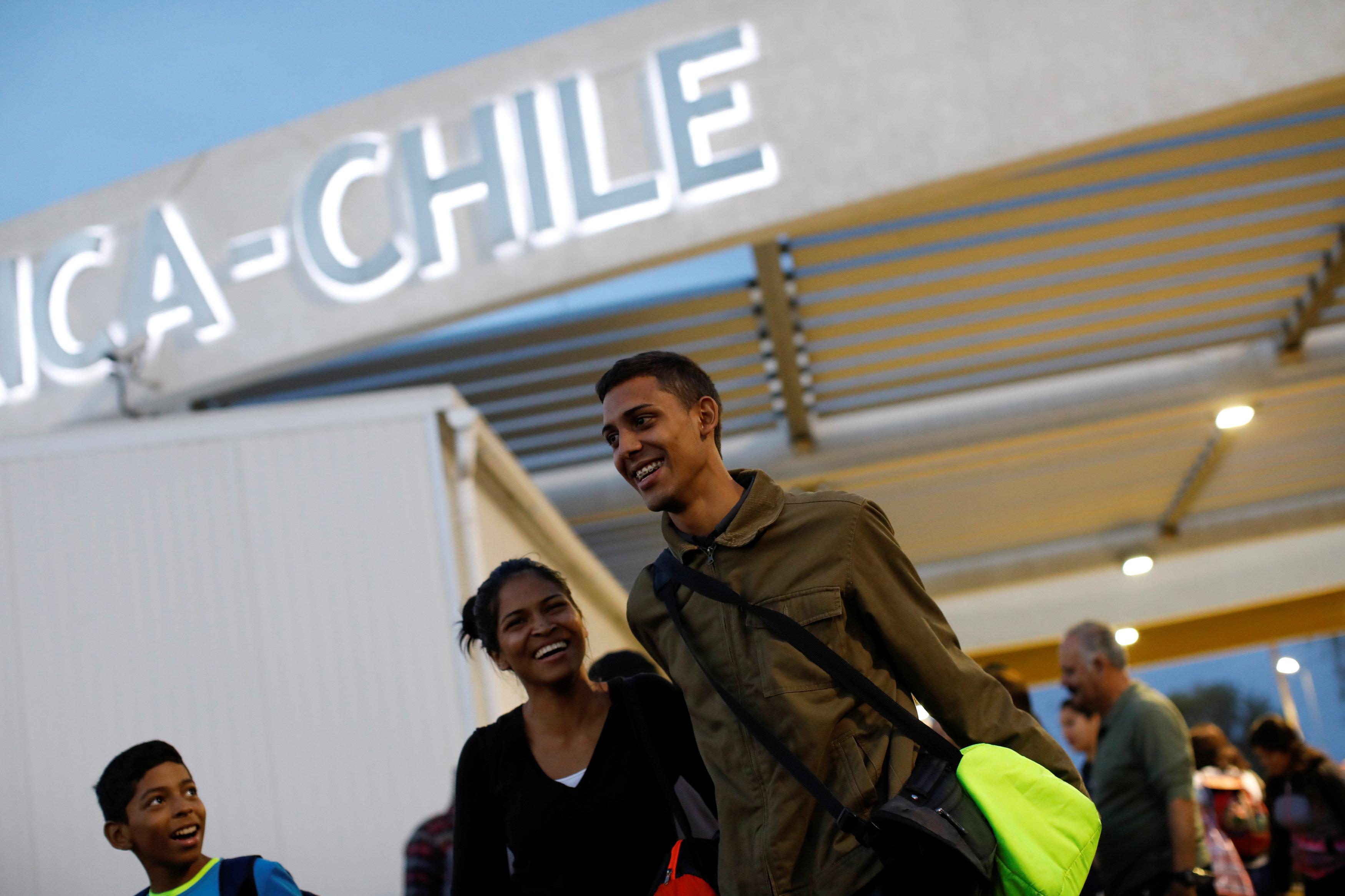 """Adrián Naveda, Alejandra Rodríguez y su sobrino David Vargas (RL), viajando en autobús desde Caracas a Chile, sonríen después de cruzar la frontera entre Perú y Chile en la oficina de migración en Arica, Chile, el 13 de noviembre de 2017. Llegar a Chile fue el objetivo, pero todos estaban un poco preocupados, porque sabían que esta era la frontera donde las autoridades podían hacerles preguntas difíciles. Mientras salían de la oficina de migración en Arica, la felicidad y el estado de ánimo de """"¡Lo logramos!"""" se hizo cargo, a pesar de que todavía tenían dos días más en el camino delante de ellos. REUTERS / Carlos Garcia Rawlins BUSCA """"RAWLINS BUS"""" PARA ESTA HISTORIA. BUSCA """"IMAGEN MÁS AMPLIA"""" PARA TODAS LAS HISTORIAS."""