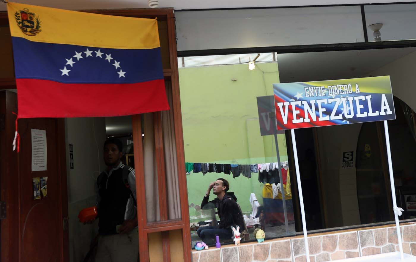 Venezuelan migrants stand next to a sign reading: ' Send money to Venezuela' at a shelter for Venezuelans in San Juan de Lurigancho, on the outskirts of Lima, Peru March 9, 2018. REUTERS/Mariana Bazo