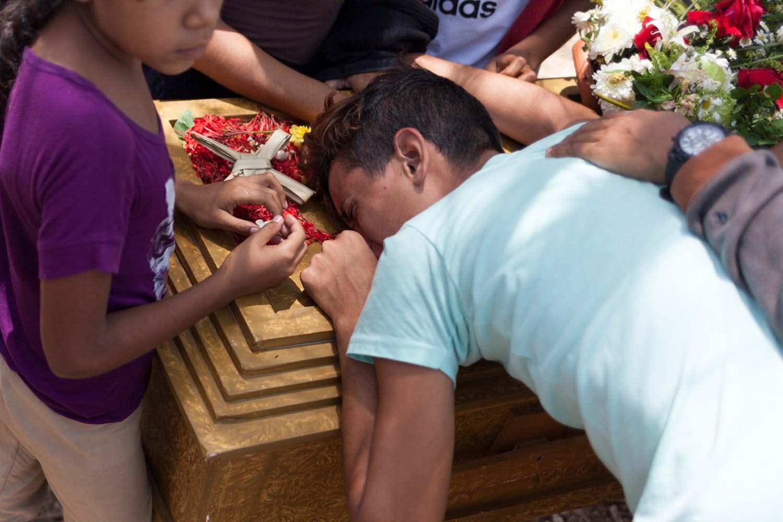 Los deudos lloran junto al ataúd de José Rivero, uno de los presos que murió durante un motín y un incendio en las celdas del Comando General de la Policía de Carabobo, durante su funeral en el cementerio de Valencia, Venezuela el 30 de marzo de 2018. REUTERS / Adriana Loureiro