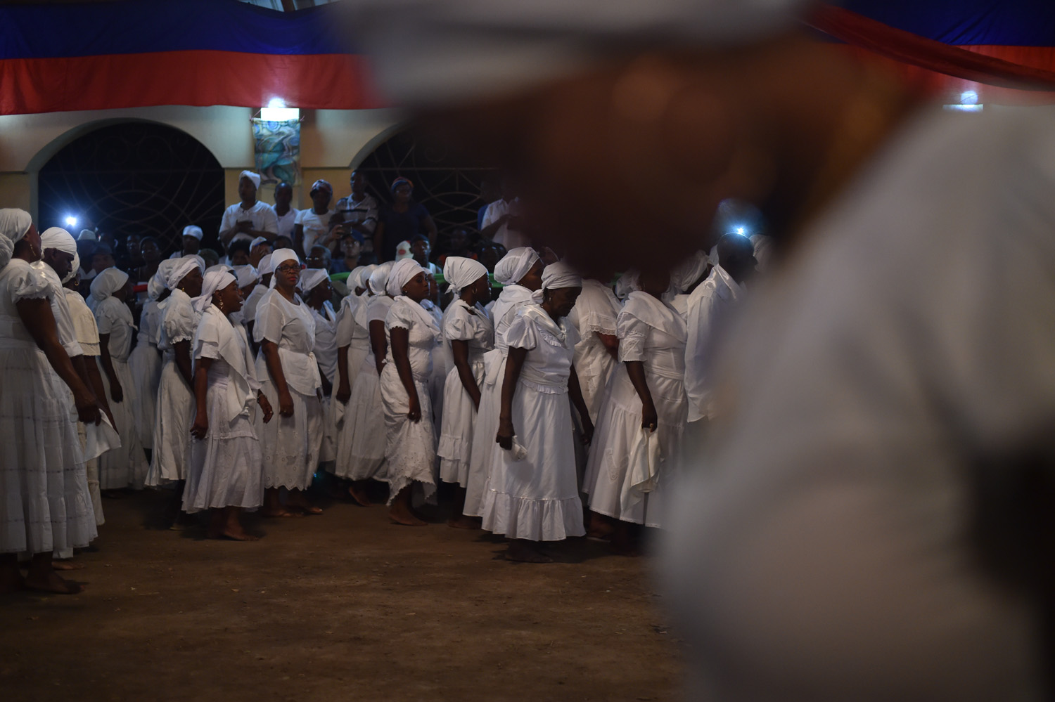 Haitian voodoo followers wearing white clothes dance while participating in a voodoo ceremony in Souvenance, a suburb of Gonaives, 171km north of Port-au-Prince, on March 31, 2018. Haitian voodoo followers arrived in Souvenance to take part in the voodoo ceremonies held during Easter weekend. / AFP PHOTO / Hector RETAMAL