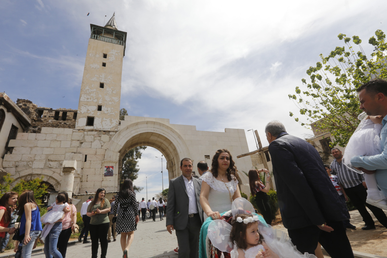 Syrian people walk down a street during a parade celebrating Easter in the Christian neighbourhood of Bab Sharqi in Old Damascus on April 1, 2018. / AFP PHOTO / Louai Beshara