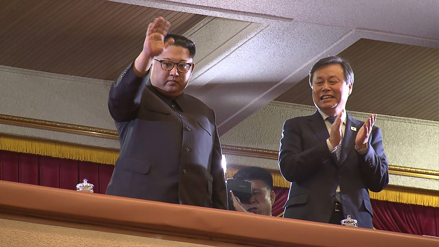 This picture captured from a video footage by Korea Pool reporters shows North Korean leader Kim Jong Un (L) and South Korea's Culture, Sports and Tourism Minister Do Jong-whan (R) during a rare concert by South Korean musicians at the 1,500-seat East Pyongyang Grand Theatre in Pyongyang on April 1, 2018. North Korean leader Kim Jong Un on April 1 attended the first concert in Pyongyang for over a decade by South Korean entertainers, including a K-pop girlband, the latest gesture of reconciliation before a rare inter-Korean summit.  / AFP PHOTO / KOREA POOL / - / South Korea OUT