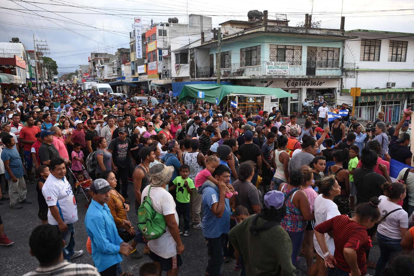 """Central American migrants taking part in a caravan called """"Migrant Viacrucis"""" towards the United States march to protest against US President Donald Trump's policies as they remain stranded in Matias Romero, Oaxaca State, Mexico, on April 3, 2018.  The hundreds of Central Americans in the """"Way of the Cross"""" migrant caravan have infuriated Trump, but they are not moving very fast -- if at all -- and remain far from the US border. As Trump vowed Tuesday to send troops to secure the southern US border, the caravan was camped out for the third straight day in the town of Matias Romero, in southern Mexico, more than 3,000 kilometers (1,800 miles) from the United States.  / AFP PHOTO / VICTORIA RAZO"""